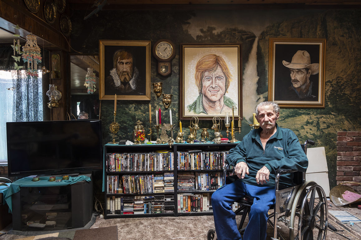 Artist Monty Brannigan with three of his celebrity portraits (Charlton Heston, Robert Redford, Tom Selleck). Photo: Kim Stringfellow.